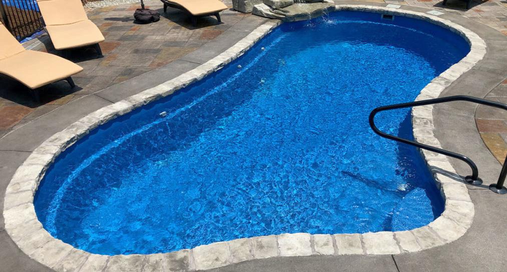 Custom shaped concrete swimming pool with stone coping