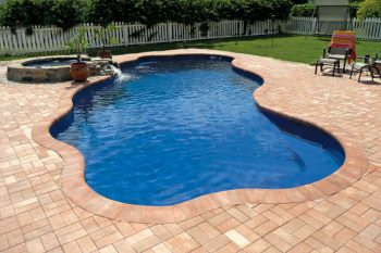 Free-form iberglass swimming pool with cobblestone decking