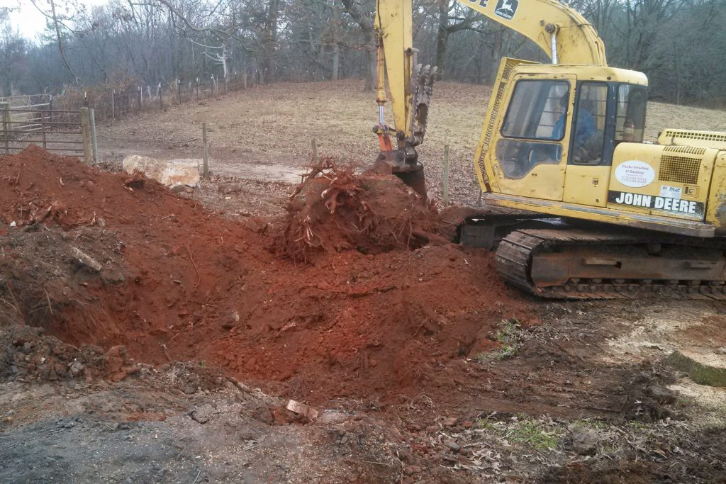 An excavator breaking ground for an in-ground pool
