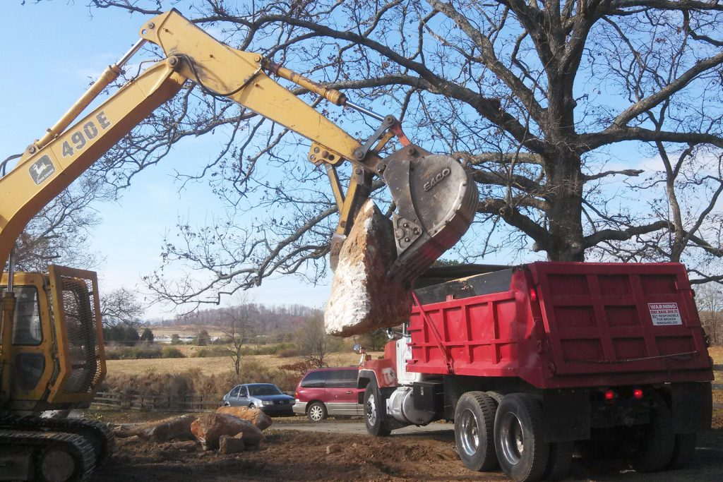 Large rock being moved from excavator machine to dump truck