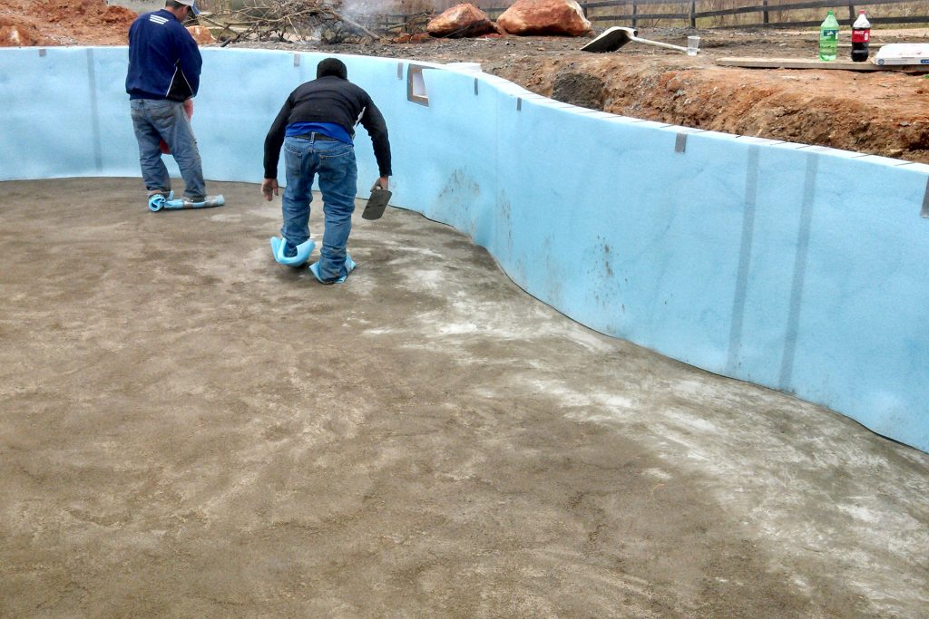 Troweling the concrete during a swimming pool installation