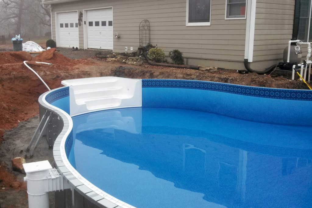Swimming pool under construction with liner installed and water filling