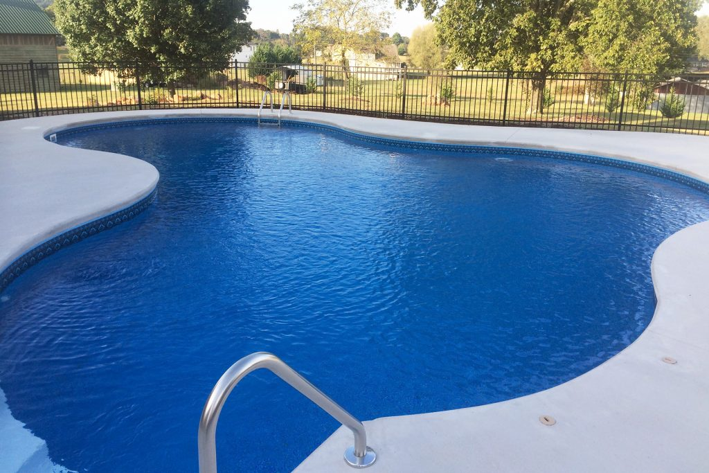 Freshly installed swimming pool with concrete fencing and wrought iron fence.