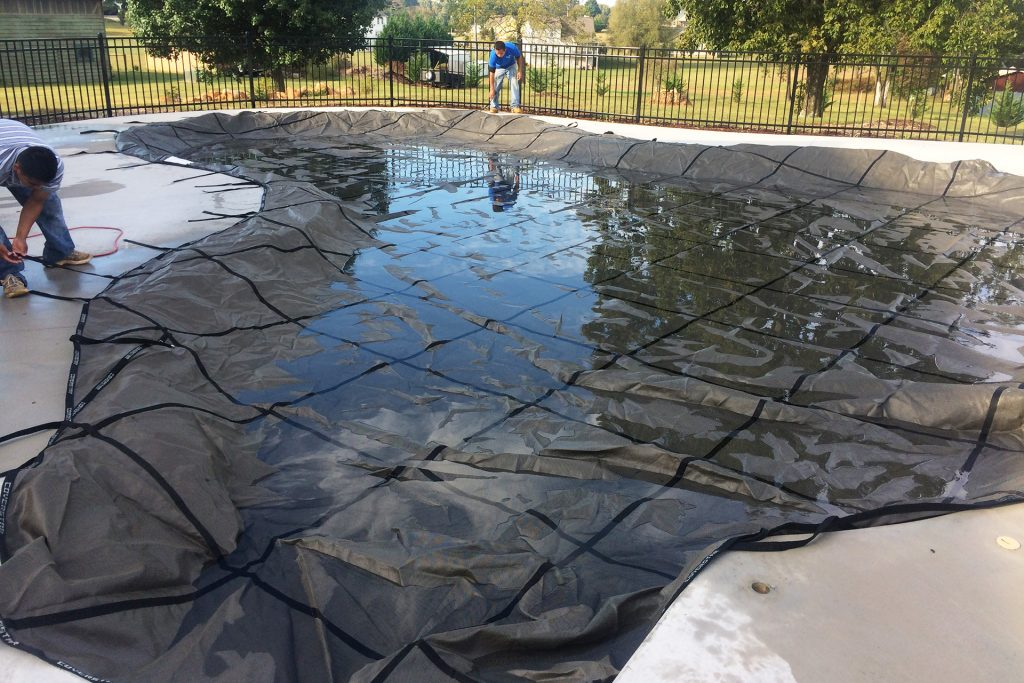 Installing a taught, mesh safety pool cover